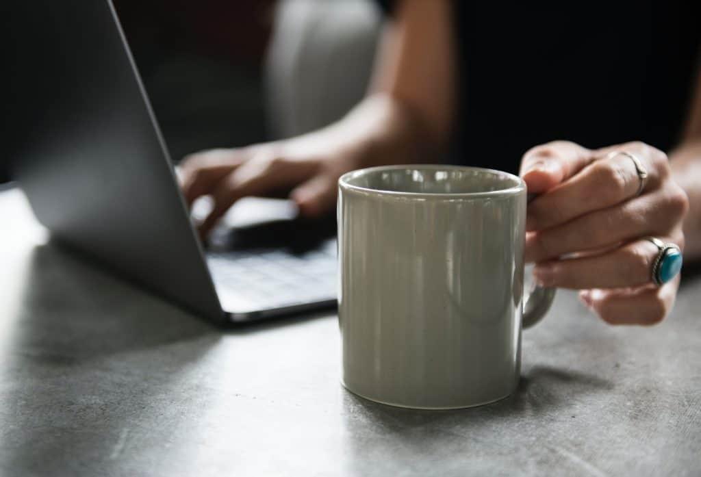 Kafeetasse vor Laptop.